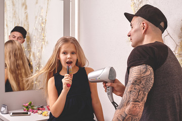 Cute little daughter and her tattoed dad are playing