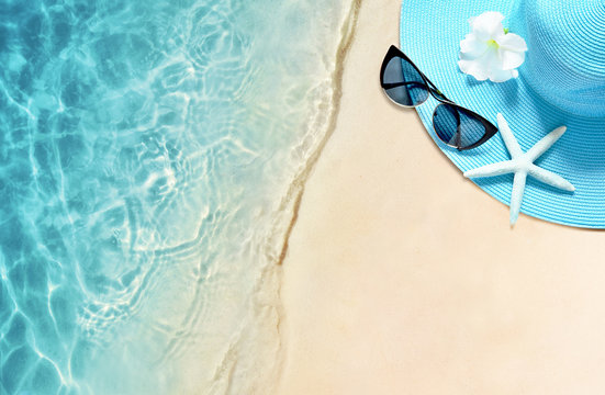 Hat and sunglasses on the sandy beach. Summer background