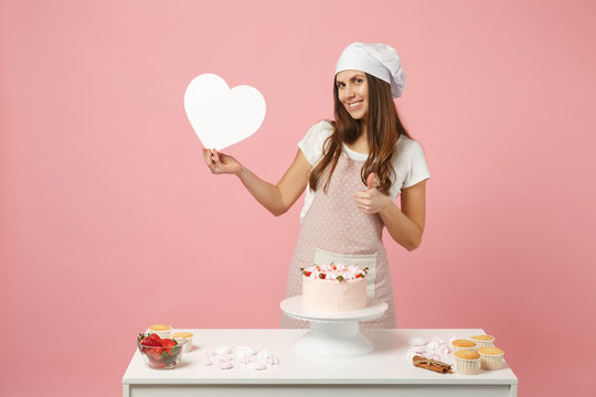 Chef cook confectioner or baker in apron white t-shirt, toque chefs hat cooking cake or cupcake at table hold like heart isolated on pink pastel background in studio. Mock up copy space food concept.