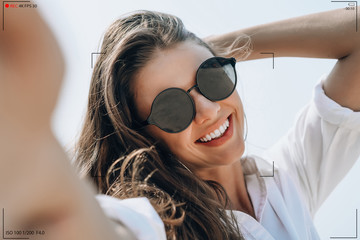 Smiling young woman in sunglasses holding camera and smiling make selfie recording video vlog from hands with mirrorless camera on the beach.Making Vlog, Blogger beauty business Concept.