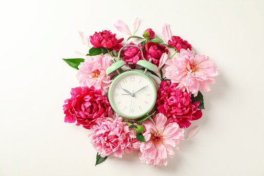 Flat lay composition with beautiful peonies and alarm clock on white background, space for text