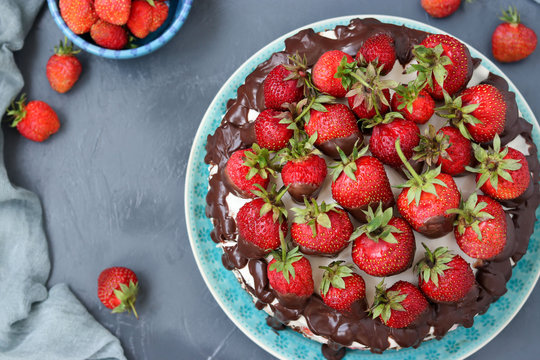 Chocolate cake with strawberries and cream located on a dark background, top view
