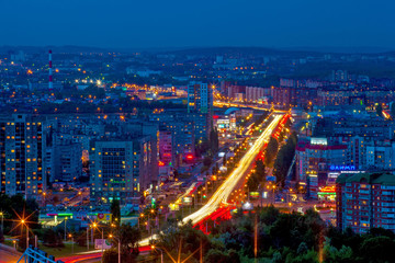 Panorama of the night modern city, the central street in the yellow light trails of passing cars between the sleeping areas in blue twilight color. Ufa, Bashkortostan, Russia - June 2015.