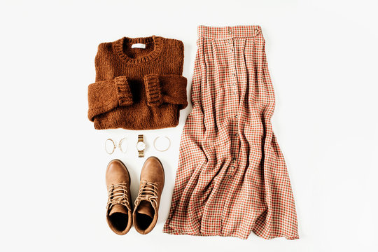 Fashion clothes look composition with brown sweater, shoes, skirt on white background. Flat lay, top view.