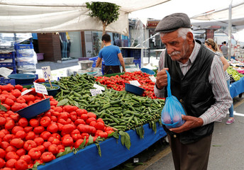 A man carries his shopping bag at a bazaar in Istanbul