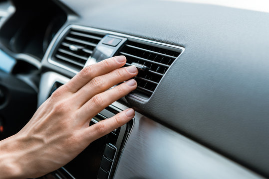 cropped view of man touching air conditioner switch in car