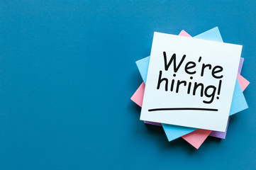 WE ARE HIRING CONCEPT ON bright background at new job place. Empty space for text