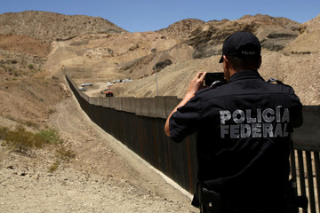 Mexican police take pictures of a bollard-type wall along the border of a private property as seen from Ciudad Juarez