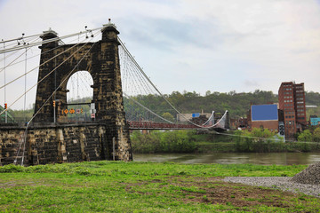 The Wheeling Suspension bridge is a historic landmark that spans the Ohio river into Wheeling , West Virginia.