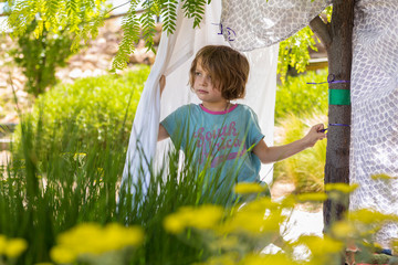 5 year old boy playing in his bed-sheet tent in backyard Wall mural