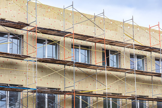 exterior wall thermal protection. building facade under renovation with scaffolding.