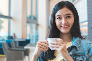 Asian woman in a cafe drinking coffee .Portrait of Asian woman smiling in coffee shop cafe vintage...