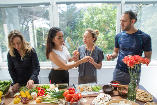 Playful people cooking vegetables in kitchen. Man and women standing at table with fresh vegetables and window with green view in background. Healthy cooking concept. Front view.