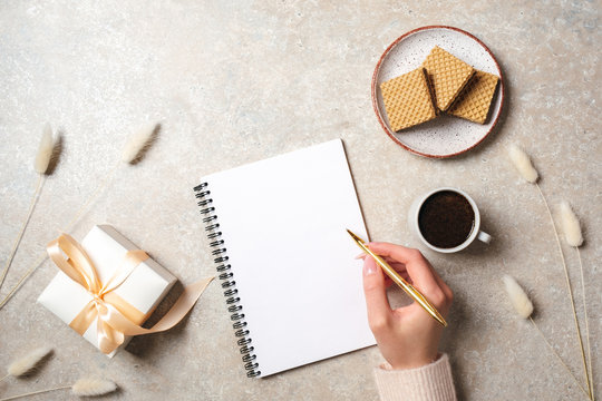 Modern minimal home workspace desk with human hand writing text message on blank paper notebook, waffles, dry flowers on concrete stone background. Flat lay style, top view fashion lifestyle blog hero