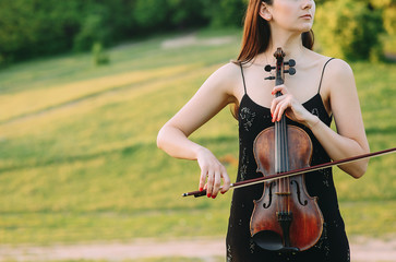 A young woman playing the violin in the field