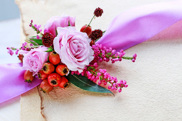 Roses, heather and hawthorn berries in small bouquet.