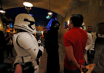 "A man takes photos of people dressed as stormtroopers and the character Kylo Ren at ""Star Wars: Galaxy's Edge"" at Disneyland Park in Anaheim"