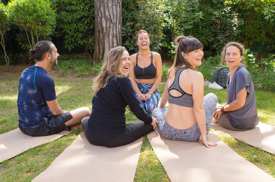 Team of friends coming together for outdoor yoga class. Man and women in fitness apparels sitting on grass and mats, looking away, smiling and laughing. Outdoor workout concept