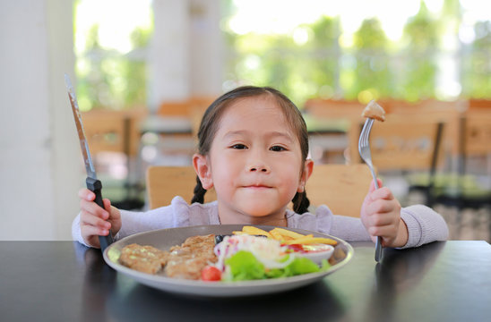 Portrait of happy Asian child girl eating Pork steak and vegetable salad on the table with holding knife and fork. Children having breakfast.