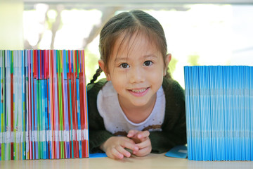Happy little Asian child girl lying on bookshelf at library. Children creativity and imagination concept.