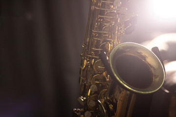 Photo sur Toile Musique Saxophone on the stand with volume light in the dark background