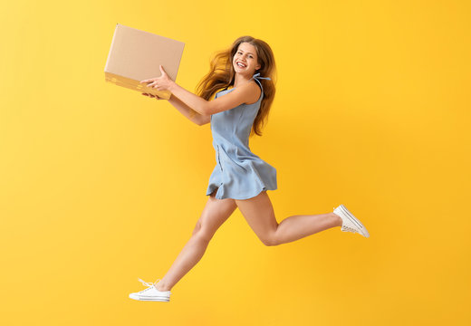 Jumping woman with cardboard box on color background