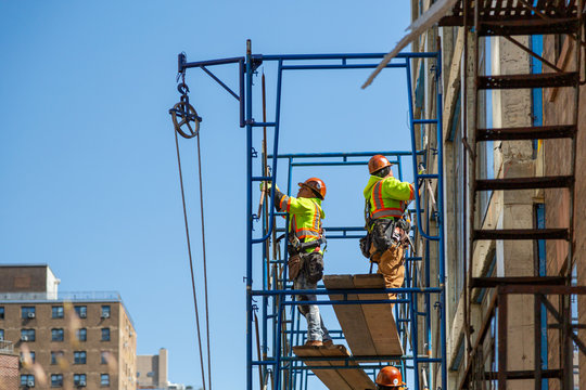 Construction workers at work on a skyscraper building renovation and construction site on a scaffold