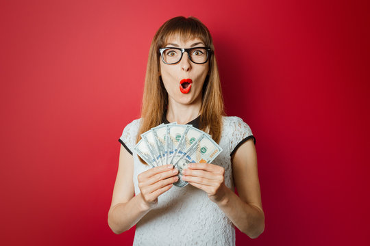 Young woman with a surprised face is holding money in the hands of a dark red background. Concept rich, winnings, lottery, credit, confirmation