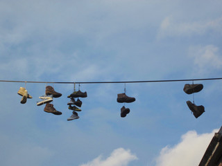 seven pair of shoes hanging on an electricity cable above the street