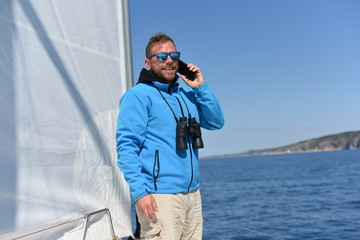 Man sailing with sails out on a sunny day and talking on the phone