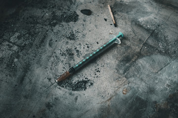 Heroin syringe on rough concrete, dirty background