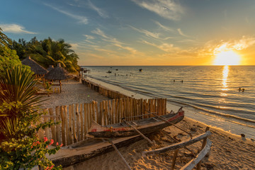 The beach of Ifaty, Mangily, near Toliara / Tulear South West Madagascar. Tropical sandy beach, thatched huts, exotic vegetation, traditional wooden fishing boat, people swimming and beautiful sky