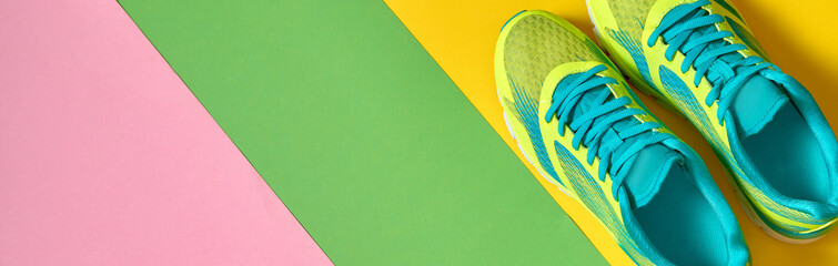 Pair of sport running shoes on colorful background. New sneakers on green, yellow and pink background, copy space. Overhead shot. Top view, flat lay