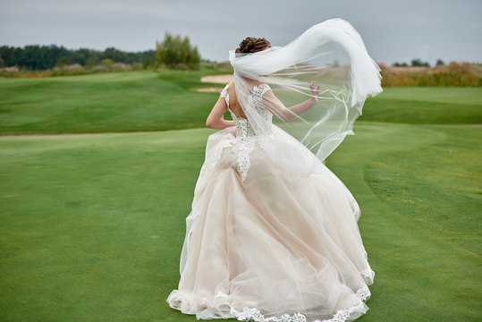 Full length body portrait of beautiful bride in white wedding dress with long veil running on green golf course, back view. Wedding concept