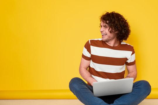 Cheerful male student using laptop