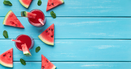 Watermelon juice and slices on blue wooden background