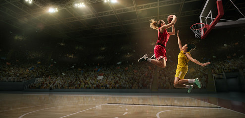Female basketball players fight for the ball. Basketball player makes slam dunk on big professional arena during the game Wall mural