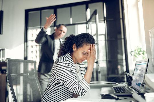 Employee having headache listening to angry boss