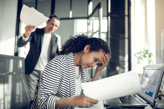 Dark-eyed employee feeling guilty for not completing the task