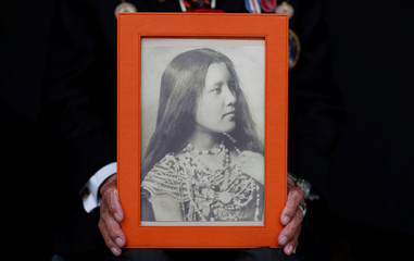 Charles Norman Shay, 94, a Penobscot Native American Indian WWII veteran, poses holding a picture of his mother Florence as he attends an interview with Reuters in Bretteville l'Orgueilleuse