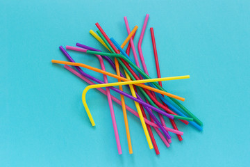 Pile of plastic disposable multi colored drinking straws for cocktails and drinks on blue background. Top view Copy space