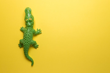 Green crocodile toy on bright yellow background. Minimal art concept.