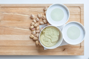 Three cup of pistchio ice cream on kitchen table background with pistachio