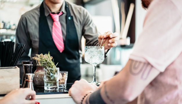 Bartender preparing gin tonic cocktail - People having fun in american bar waiting for barman serving drinks - Concept of youth lifestyle and bar entertainment