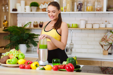 Woman Making Healthy Juice With Machine In Kitchen