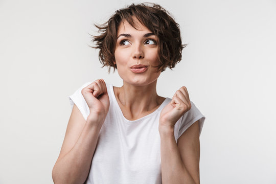 Portrait of excited woman with short brown hair in basic t-shirt rejoicing and clenching fists