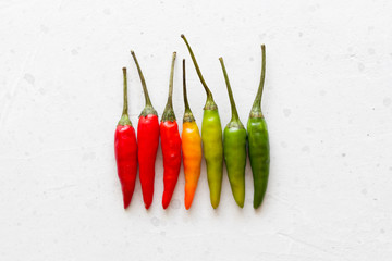 Red Hot Chili Peppers On Background or White Table. A Lot of Red Chilli Peppers. Green, Yellow Hot Chili Peppers. Copy space for your text. Flat lay, top view. Colorful chili pepper rainbow. Gradient