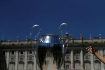 People have their picture taken next to a giant replica of the UEFA Champions League trophy that is displayed outside the Royal Palace in Madrid
