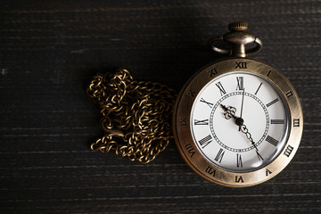 Antique pocket watch Placed on a black wooden background. copy space for text