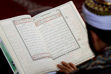A man reads the Koran at the Grand Mosque, during the holy month of Ramadan in Sanaa